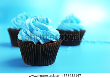 Chocolate cupcakes on blue background - stock photo