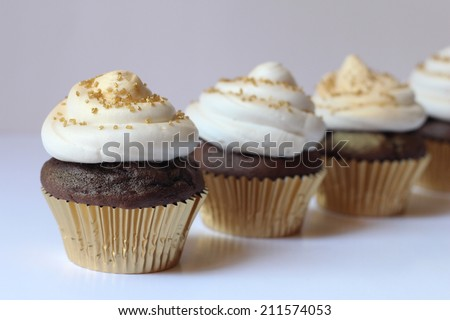 Chocolate Cupcakes with butter-cream frosting in gold cupcake liners - stock photo