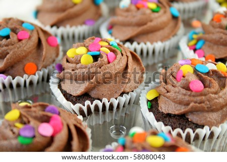 Chocolate cupcakes with colorful sprinkles.  Used a shallow DOF with selective focus. - stock photo