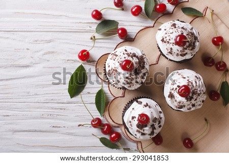 Chocolate cupcakes with cream and fresh cherry Black Forest on the table. horizontal top view  - stock photo