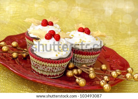 Chocolate cupcakes with vanilla icing decorated with gold colored fondant leaves and red candy. - stock photo