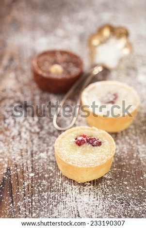 Chocolate dark and white Mini Tartlets in rustic style on wooden sugar dusted table, shallow dof - stock photo