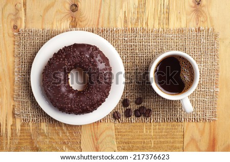 Chocolate donut and cup of hot coffee on vintage wooden table. Top view - stock photo