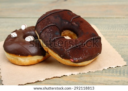 Chocolate donuts on wooden background - stock photo