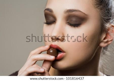 Chocolate dreams, artistic portrait of brunette eating bonbons. - stock photo