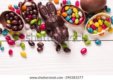 Chocolate Easter eggs and rabbit , on wooden background - stock photo