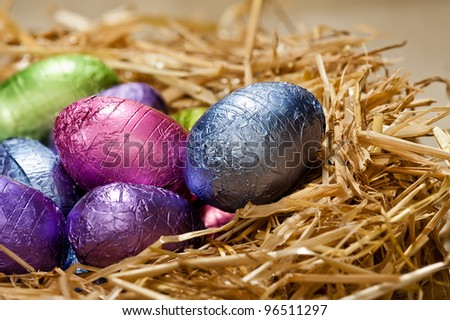 Chocolate Easter eggs in a natural straw nest a nice close-up shoot - stock photo
