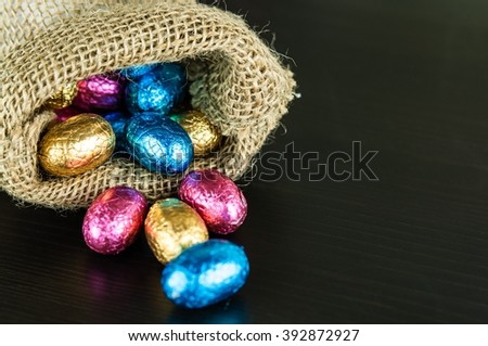 Chocolate Easter eggs in colorful foil on dark background scattered from small jute bag, space for text - stock photo