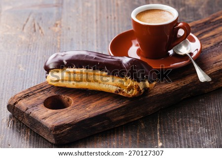Chocolate eclair and coffee cup on dark wooden background - stock ...