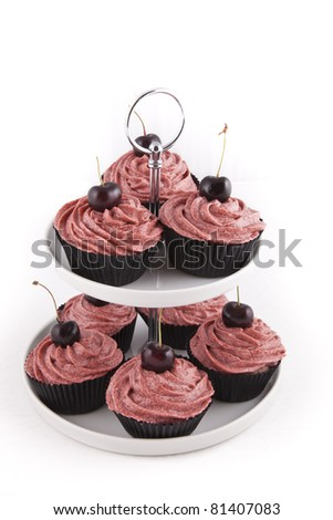 Chocolate flavored cupcakes, with red frosting and a cherry on top, on a cupcake stand on white background - stock photo