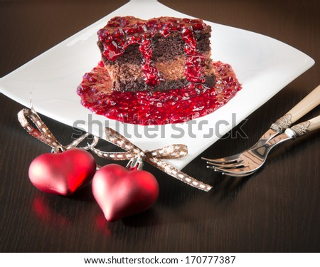 Chocolate ganache mousse cake with raspberry sauce for two on Valentines day. - stock photo