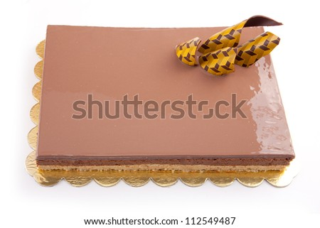 Chocolate glossy light cake on white stuffed with nuts - stock photo
