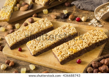 Chocolate granola bars with cornflakes, puffed cereals and rolled oats on wooden cutting board - stock photo