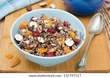Chocolate granola with nuts and dried fruit on a wooden board horizontal - stock photo