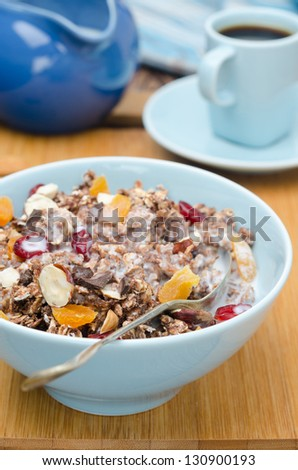 Chocolate granola with nuts, dried fruit and milk on a wooden board closeup - stock photo