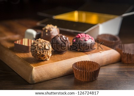 Chocolate handmade candies on a kitchen table. Chocolate box open. - stock photo