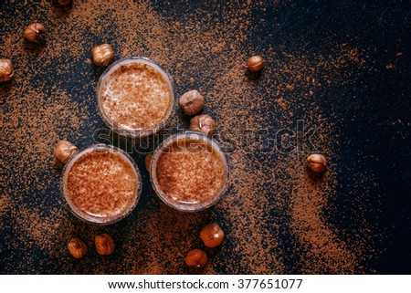Chocolate-hazelnut smoothie with banana in glasses sprinkled with ground cocoa, top view - stock photo