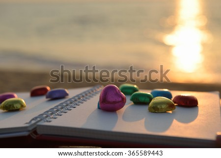 Chocolate heart shape  colorful laying on book at beach sunset - stock photo
