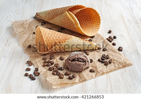 Chocolate ice cream and waffle cone on parchment paper - stock photo