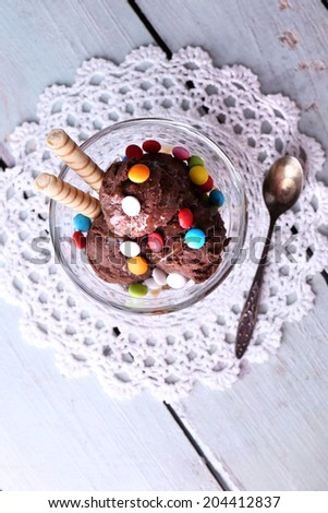 Chocolate ice cream with multicolor candies and wafer rolls in glass bowl, on color wooden background - stock photo