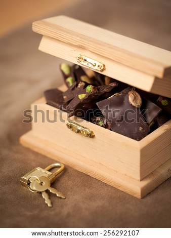 Chocolate in the chest with lock and keys - stock photo