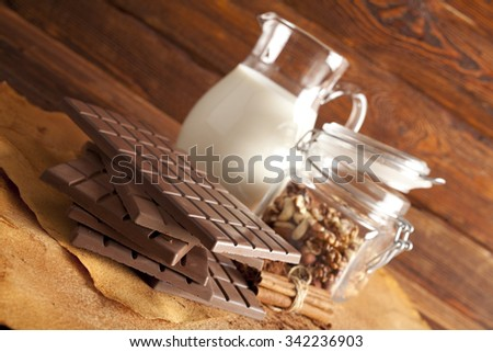 Chocolate, jug of milk, cinnamon, cocoa and mixed nuts in a jar - stock photo