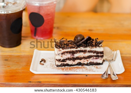 Chocolate Layer Cake with cool drinks background on the wooden table, soft warm color tone.  - stock photo
