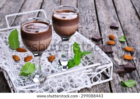 Chocolate liqueur in the traditional glasses on a wooden surface - stock photo