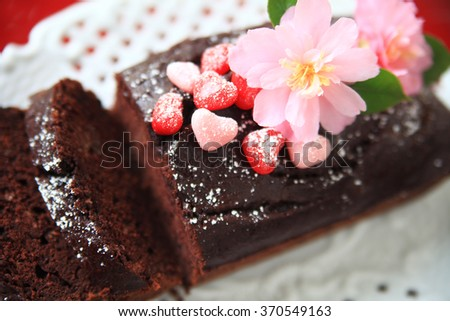 Chocolate loaf cake decorated with powdered sugar, candy hearts and fresh camellias - stock photo