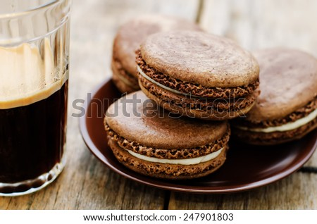 chocolate macaron with cream cheese and coffee on a dark wood background. tinting. selective focus - stock photo