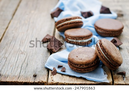 chocolate macaron with cream cheese on a dark wood background. tinting. selective focus - stock photo