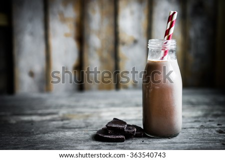 Chocolate milk in a jar on wooden background - stock photo