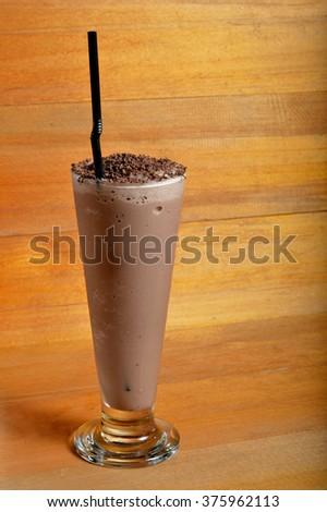 chocolate milkshake drink on wooden board - stock photo
