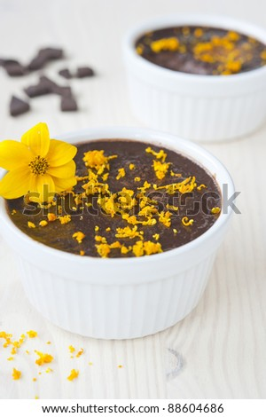 chocolate mousse in two tins of white, sprinkled with orange zest and decorated with a yellow flower on a wooden table, near the spill zest and slices of chocolate, vertical frame - stock photo