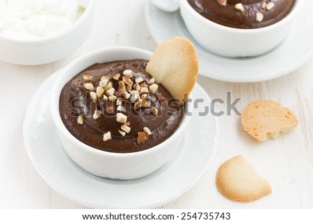 chocolate mousse with biscuits and nuts in white cups, top view, horizontal - stock photo