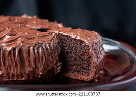 Chocolate Mud Cake on red serve dish on black background - stock photo