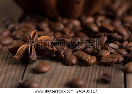Chocolate muffin, coffee beans, cinnamon, star anise on sacking background. - stock photo