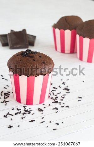 Chocolate muffins in pink striped muffin paper on a table with chocolate pieces. - stock photo