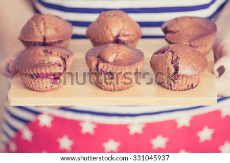 Chocolate muffins with berries in the hands of women - stock photo