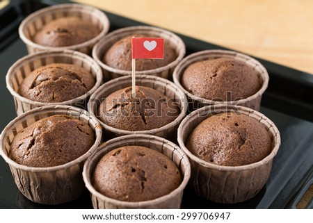 Chocolate muffins with small flag of love - stock photo