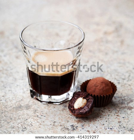 Chocolate nut truffles and glass of espresso, selective focus - stock photo