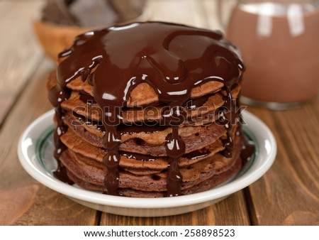 Chocolate pancakes on a brown background - stock photo