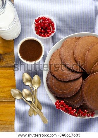 chocolate pancakes on a wooden table. ripe currants and fresh milk. preparing a healthy breakfast - stock photo