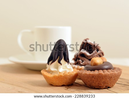 chocolate pastry with a White coffee cup on a wooden board close up shallow dof - stock photo