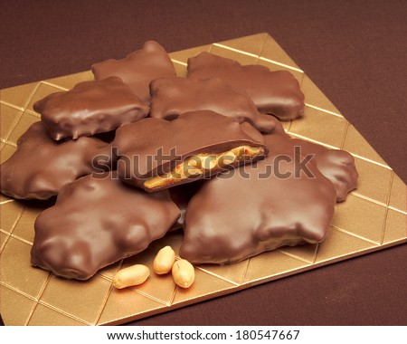 Chocolate Peanut Clusters on Gold Tile with Whole Peanuts and Caramel on Brown Service Setting; Chocolate Brittle: Peanut - stock photo