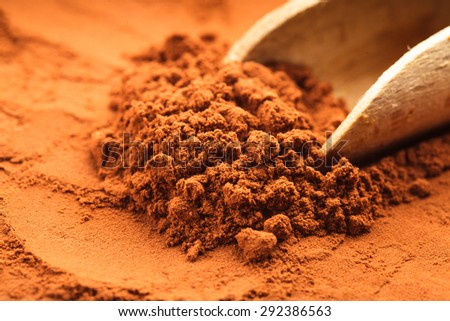 chocolate powder heap and wooden scoop close up - stock photo