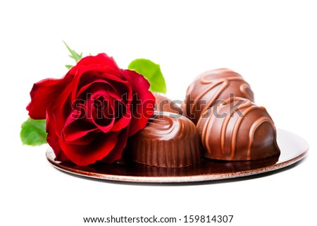 Chocolate pralines and red rose on white background - stock photo