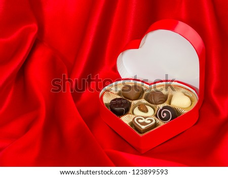 chocolate pralines in golden heart shape box over red silk background - stock photo