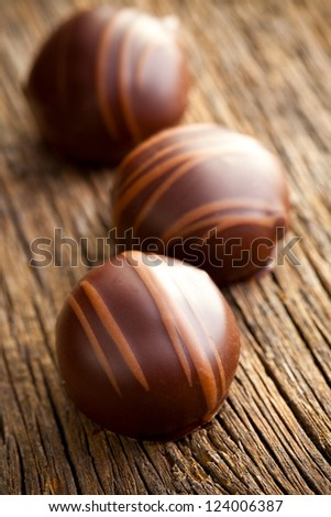 chocolate pralines on old wooden table - stock photo