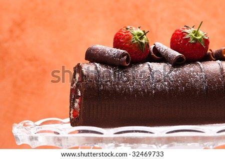 Chocolate roulade with strawberries with orange background - stock photo